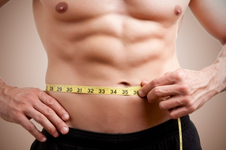 Fit man measuring his waist after a workout in the gym photo