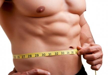 hombre flaco: Hombre apto medir su cintura después de un entrenamiento en el gimnasio, aislado en un fondo blanco Foto de archivo