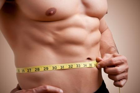 Fit homme mesurant son tour de taille après une séance d'entraînement dans le gymnase