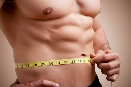 Fit man measuring his waist after a workout in the gym Stock Photo