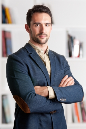 Casual business man with arms crossed with a bookshelf behind him