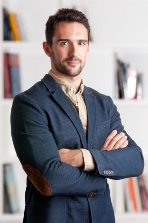 Homme d'affaires décontractée avec les bras croisés avec une étagère derrière lui Banque d'images