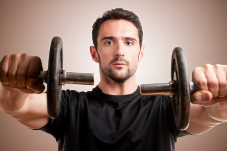 raises: Personal Trainer doing front dumbell raises for training his deltoids in a brown background