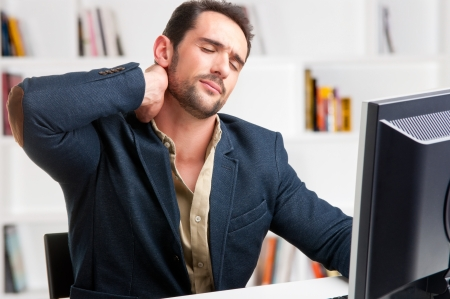 Casual businessman sitting in a desk with pain in his neck Stockfoto