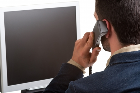 Casual businessman talking over the phone and looking at an empty computer screen, isolated in white