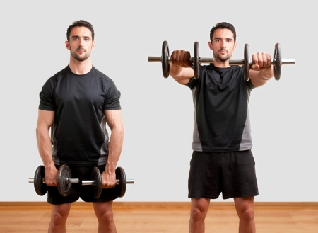 deltoids: Personal Trainer doing front dumbell raises for training his deltoids, in a gym