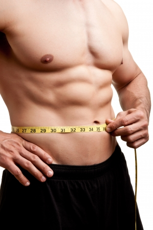 six pack abs: Fit man measuring his waist after a workout in the gym, isolated in a white background