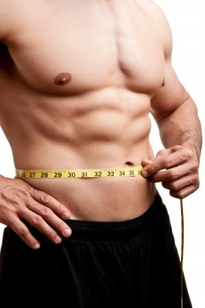 Fit muž měření jeho pasu po tréninku v posilovně, izolován v bílém pozadí