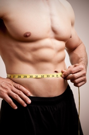 Fit man measuring his waist after a workout in the gym, in a dark brown background Stock Photo