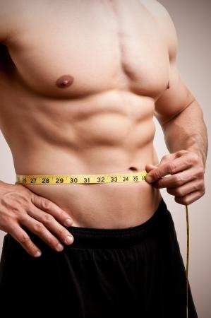 Monter homme mesurant son tour de taille après une séance d'entraînement dans le gymnase, dans un fond brun foncé