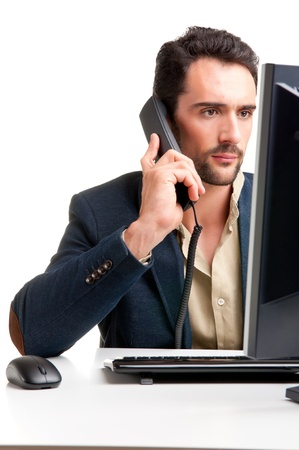 Man looking at a computer screen, on the phone, thinking about the job at hand photo