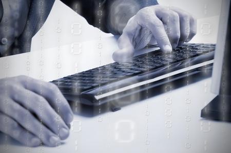 Businessman typing in a computer keyboard, blue tone, binary data overlay photo