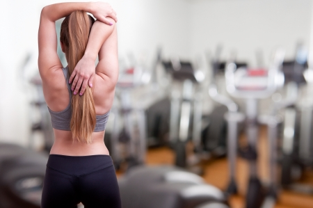 Sporty woman stretching her arm, in a gym