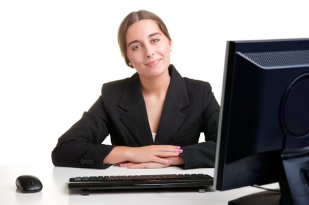 Young Businesswoman sitting at her office desk and smilling, isolated in white photo