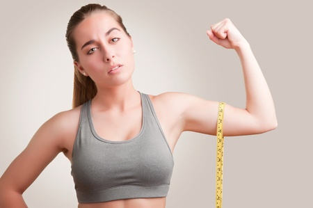 Powerful woman measuring her biceps with a yellow measuring tape photo