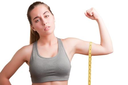 krachtige vrouw: Krachtige vrouw die haar biceps met een geel meetlint