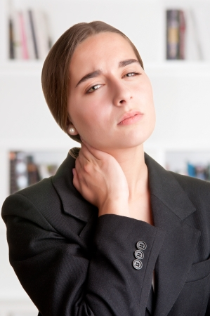 sore muscles: Young businesswoman with neck pain with a bookshelf behind her