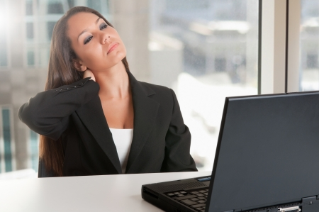 working stiff: Businesswoman sitting at her desk tired and with a painful neck, isolated in white Stock Photo