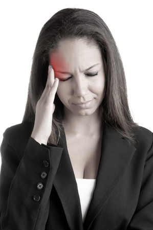 Business woman suffering from an headache, holding her hands to the head, with a red spot around painful area photo