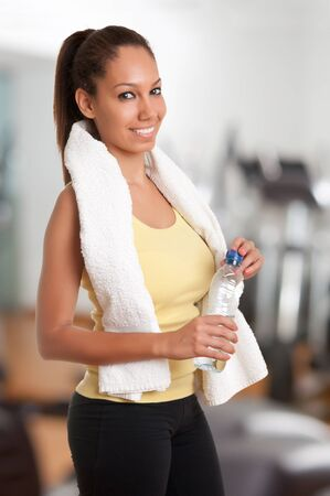 Woman holding a plastic bottle of water, dressed in sports clothes, in a gym photo