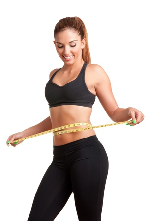Woman measuring her waist with a yellow measuring tape, isolated in white photo