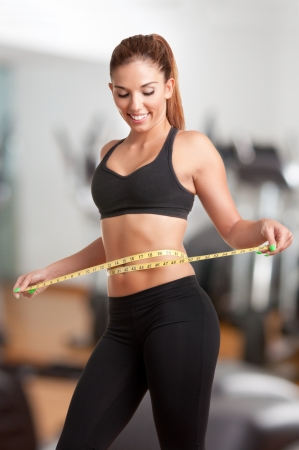 Woman measuring her waist with a yellow measuring tape, in a gym photo