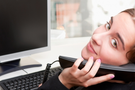 Businesswoman talking on the phone while working at a computer photo