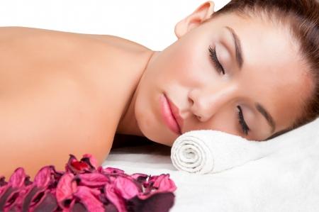 Jonge vrouw liggend in een spa klaar om een massage te krijgen, geïsoleerd in het wit Stockfoto
