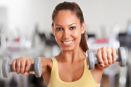 strong women: Woman working out with dumbbells at a gym