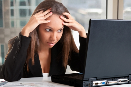 Bezorgd zakenvrouw op zoek naar een computerscherm in een kantoor Stockfoto