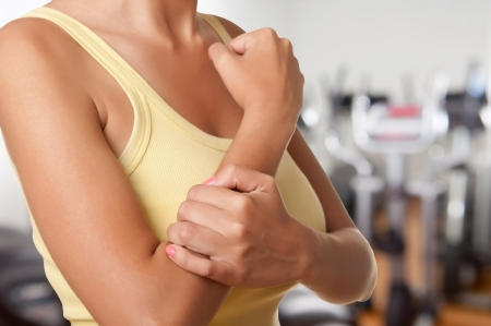 Žena s bolestí v předloktí v tělocvičně Reklamní fotografie