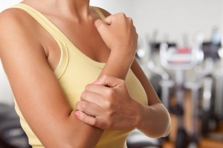 Vrouw met pijn in haar onderarm in een sportschool Stockfoto