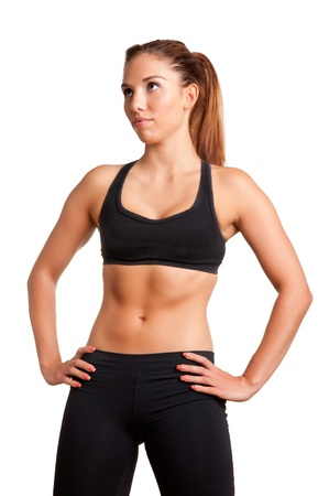 Sporty woman standing up with arms resting at her waist, looking up, isolated in white photo