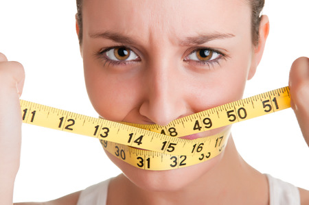 Woman with a yellow measuring tape around her mouth, isolated in white photo