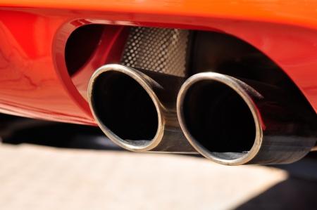 赤い車のデュアル排気管のクローズ アップ 写真素材