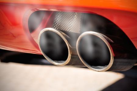 dioxido de carbono: Primer plano de un coche tubo de escape doble rojo con humo a su alrededor
