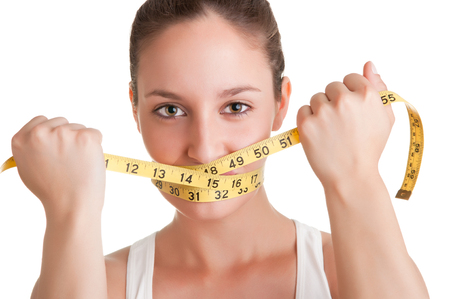 weight gain: Woman with a yellow measuring tape around her mouth, isolated in white