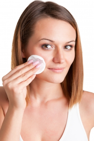 remover: Woman removing make-up with a cotton pad in front of a mirror, isolated in white