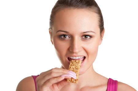 barra de cereal: Mujer joven atractiva que come una barra de cereal, aislado en blanco