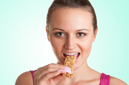 barra de cereal: Mujer joven atractiva que come una barra de cereal, en una zona verde