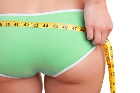 mujer celulitis: Vista trasera de una mujer medir su cintura, aislado en blanco