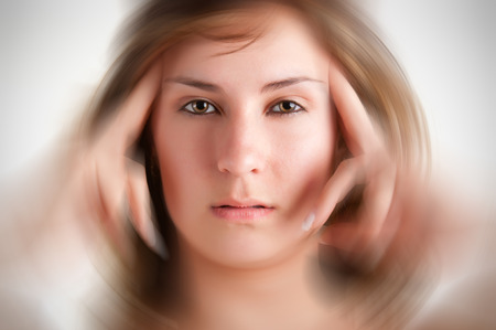 Woman suffering from an headache, holding her hands to the head, with radial blur effect applied
