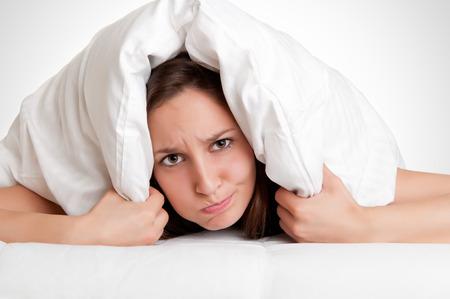 그녀의 머리 위에 베개와 여자는 침대에서 나가야하고 싶지 않다