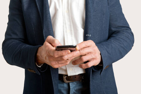 holding cell: Casual businessman sending a text message on a mobile phone Stock Photo
