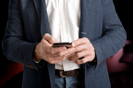 Casual businessman sending a text message on a mobile phone photo