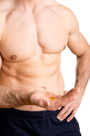 supplements: Fitness athlete taking a pill for supplementation, isolated in white