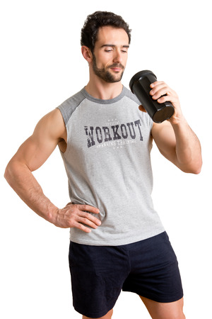Man drinking a protein shake after a workout in the gym, isolated in white photo