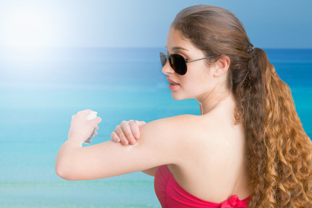Woman applying sunscreen on her arm, on the beach photo