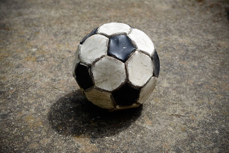 Old and used soccer ball on a cement playing field photo
