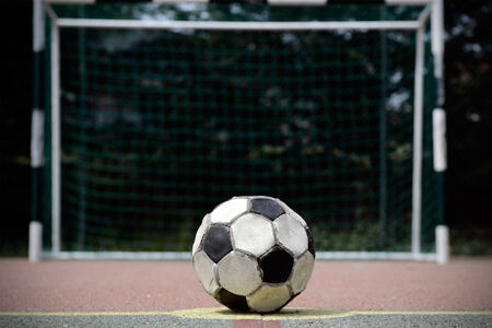 soccerball: Old and used soccer ball on a cement playing field